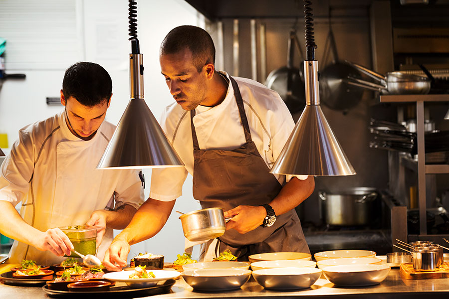 Two Chefs Standing In A Restaurant Kitchen Plating Oldbury