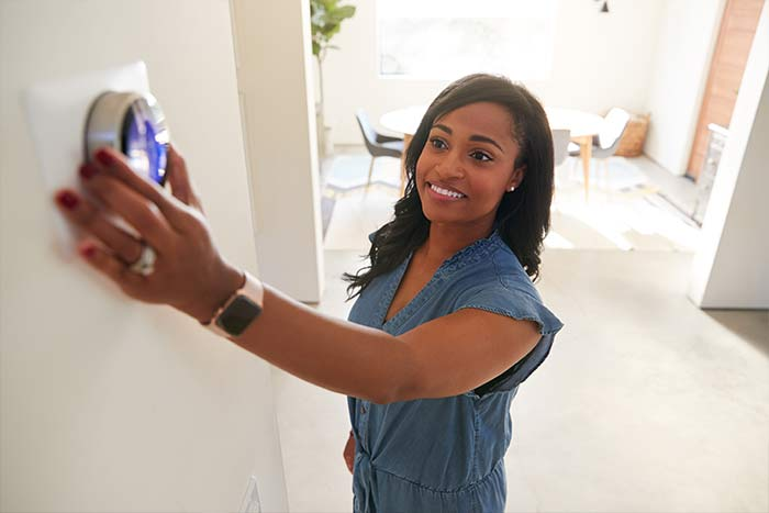 Woman Adjusting Digital Central Heating Thermostat Oldbury